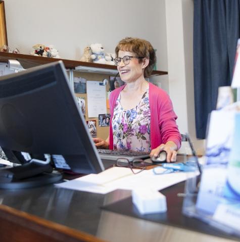 Kuvassa nainen tietokoneen ääressä hymyillen. Naisella kukkainen paita ja pinkki villaneule.