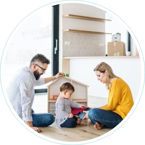 Äiti, isä ja lapsi leikkivät nukkekodilla kodin lattialla